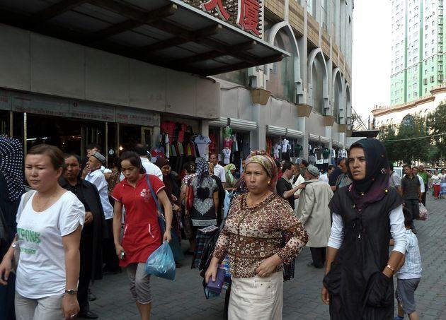 Members of Uyghur ethnic minority shop near the Erduoqiao neighborhood in Urumqi in northwestern China's...