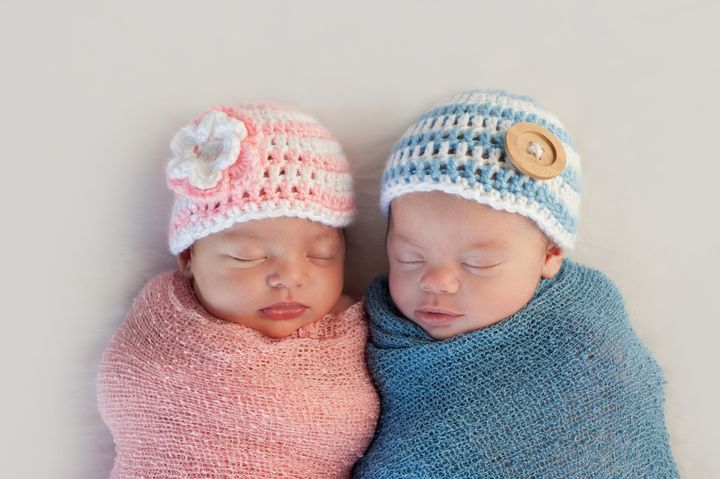 Five week old sleeping boy and girl fraternal twin newborn babies. They are wearing crocheted pink and blue striped hats.