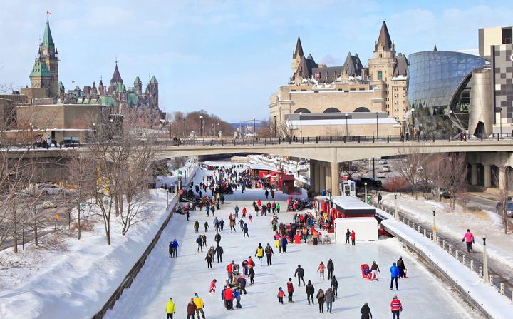 In this stock photo, skaters are seen on the Rideau Canal in downtown Ottawa, with Parliament Hill on the left.