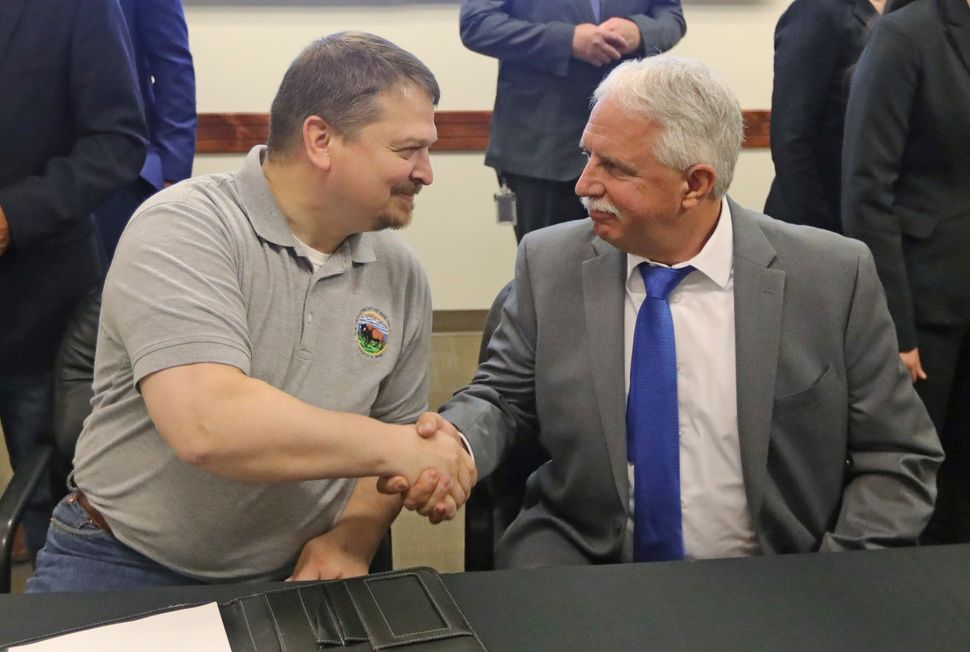 Joe Balash, left, the former assistant secretary for land and minerals management at the Interior Department, shakes hands wi