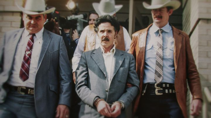 """Henry Lee Lucas (centre) being escorted by Ranger Bob Prince (left) and task force in footage from """"The Confession Killer."""""""