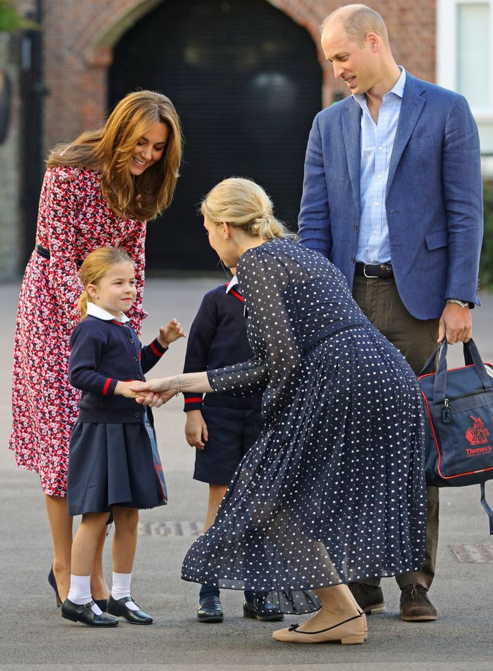 Helen Haslem, head of the lower school, greets Princess Charlotte as she arrives for her first day of school, with her brothe