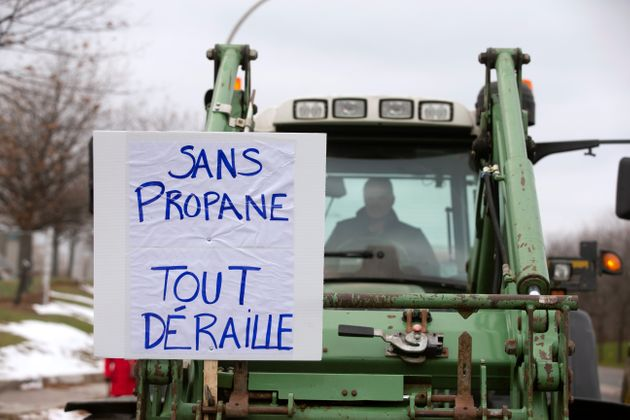 Farmers in tractors with a sign stating
