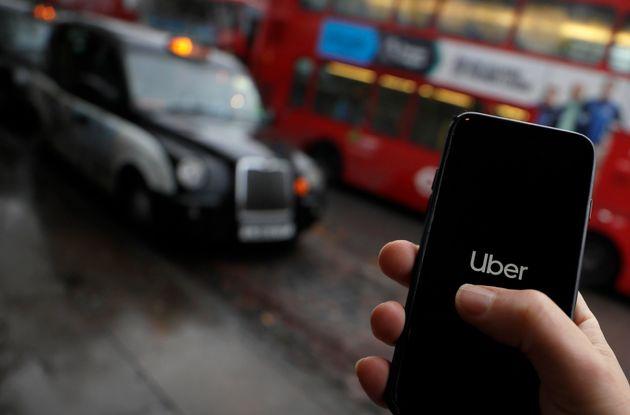Un usuario trata de pedir un servicio de Uber, ante una parada de taxis de