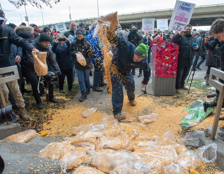 Farmers dump corn as they protest the ongoing rail strike in front of the riding office of Prime Minister Justin Trudeau on Nov. 25, 2019 in Montreal.