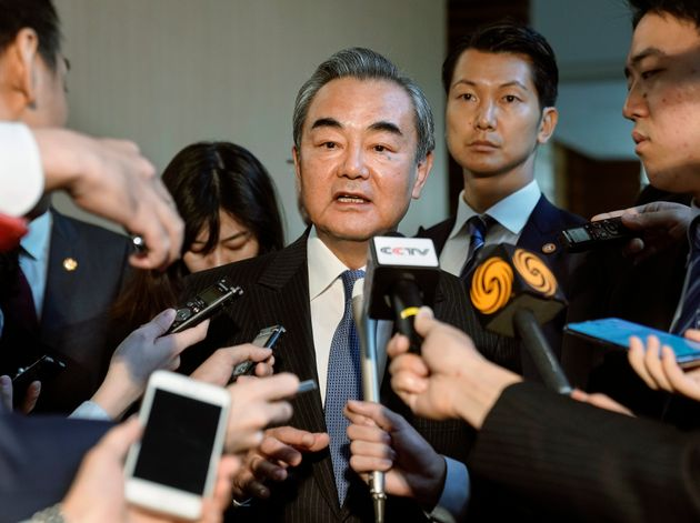 Chinese Foreign Minister Wang Yi, center, is surrounded by journalists after talks with Japanese Prime...