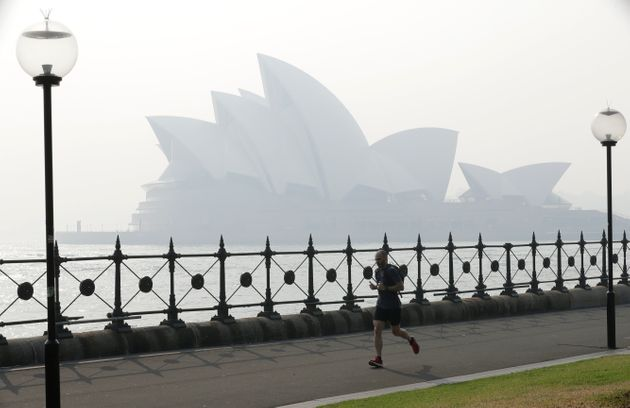 A jogger runs in the morning as smoke haze hangs over the Sydney Opera House in Sydney, on Nov. 21,