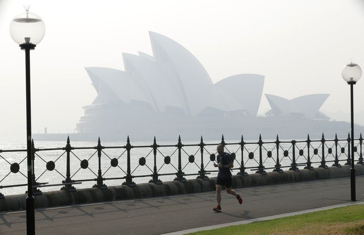 A jogger runs in the morning as smoke haze hangs over the Sydney Opera House in Sydney, on Nov. 21, 2019.