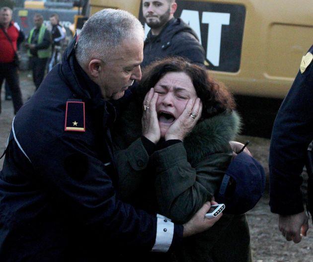 Una mujer llora porque sus parientes están atrapados en un edificio después de que un terremoto golpeara...