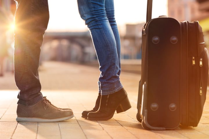 Closeup shot of woman feet standing on tiptoe while embracing her man at railway platform for a farewell before train departure. A travelling luggage is on the foreground. Beautiful warm sunset light and flare are coming from the background.