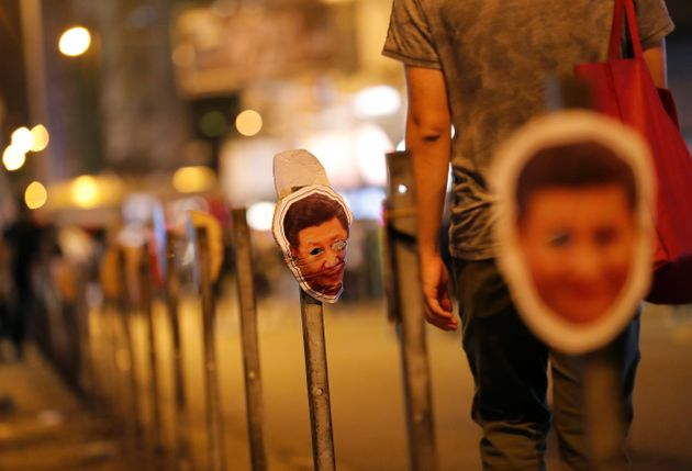 Masks depicting China's President Xi Jinping hang on guard rail on a street during anti-government protest...