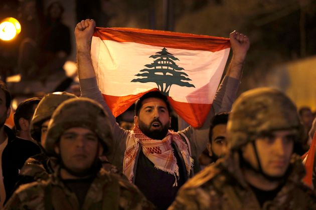 An anti-government protester holds his nation flag, as he stands behind Lebanese army soldiers during...