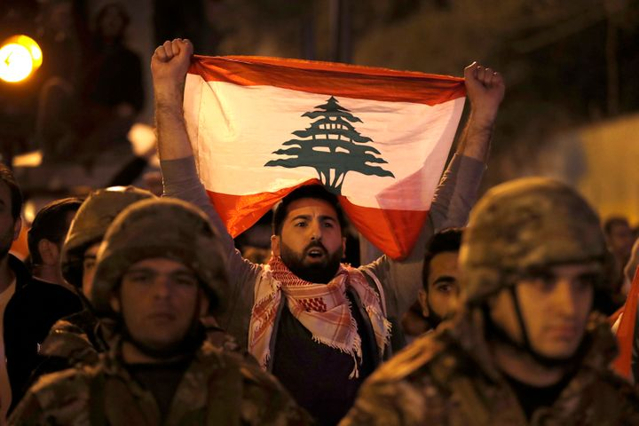 An anti-government protester holds his nation flag, as he stands behind Lebanese army soldiers during a clash between the ant