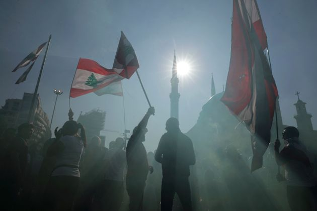 Anti-government protesters wave Lebanese national flags as gather during separate civil parade at the...