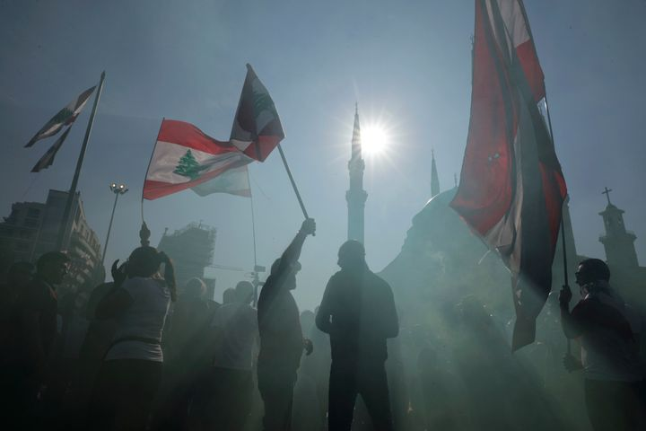 Anti-government protesters wave Lebanese national flags as gather during separate civil parade at the Martyr square, in downt