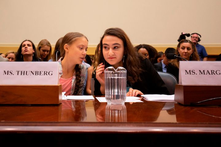 Greta Thunberg, left, talks to Jamie Margolin, right, during a joint hearing before the House Foreign Affairs Committee, Europe, Eurasia, Energy and the Environment Subcommittee, and the House Select Committee on the Climate Crisis on Capitol Hill in Washington, D.C.