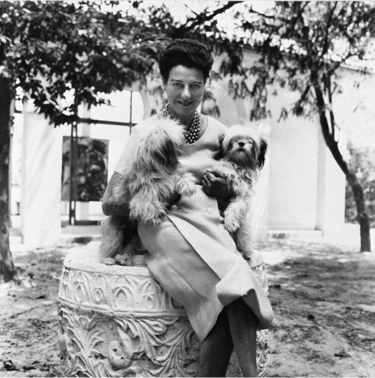 Peggy Guggenheim nel giardino di Palazzo Venier dei Leoni, Venezia, anni '50. Alle sue spalle Karel Appel, Il coccodrillo piangente cerca di afferrare il sole (The Crying Crocodile Tries to Catch the Sun), 1956.