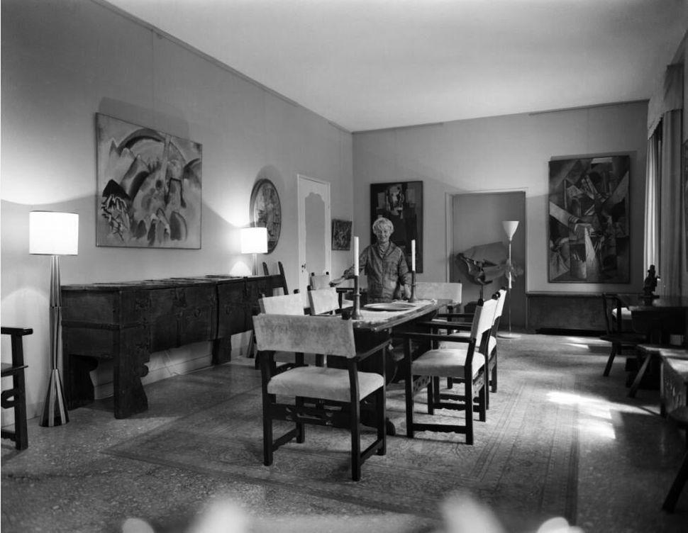 Peggy Guggenheim nella sala da pranzo di Palazzo Venier dei Leoni, Venezia, anni '60. A sinistra, Vasily&nbsp;Kandinsky, <i>Paesaggio con macchie rosse, n. 2 </i>(<i>Landschaft mit roten Flecken, Nr. 2</i>), 1913. In fondo al centro, Umberto Boccioni <i>Dinamismo di un cavallo in corsa + case</i>, 1915.&nbsp;