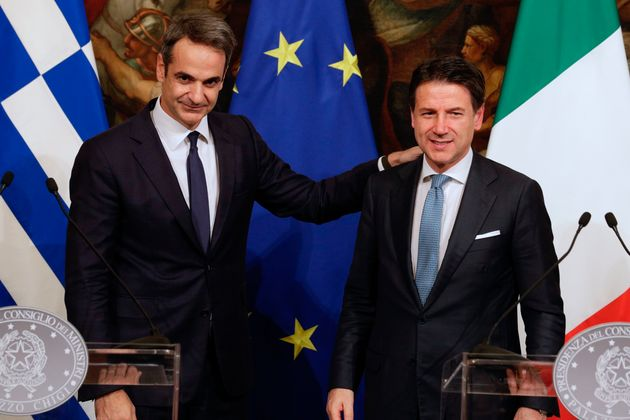 Greek Premier Kyriakos Mitsotakis shakes hands with Italian Premier Giuseppe Conte at the end of a joint...