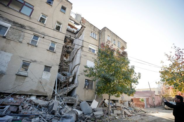 A man takes pictures of a damaged building in Durres, after an earthquake shook Albania, November 26,...
