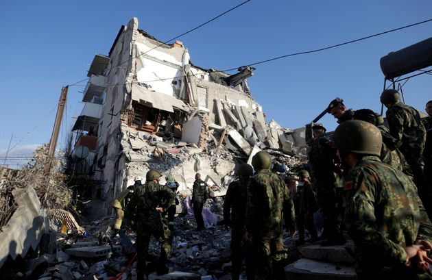 Emergency personnel work near a damaged building in Thumane, after an earthquake shook Albania, November...