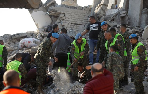 Military personnel and locals work near a damaged building in Thumane, after an earthquake shook Albania,...