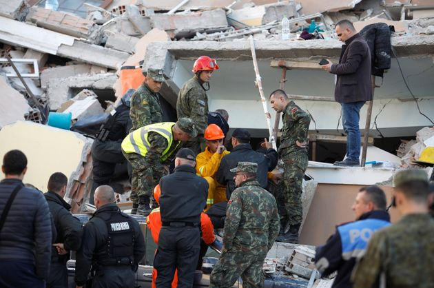 Emergency personnel talk at the site of a collapsed building in Durres, after an earthquake shook Albania,...