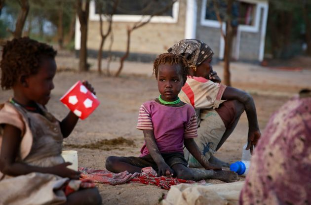 In this photo taken Sunday, March 24, 2019, Kenyan children sit down on the ground to share a meal in...