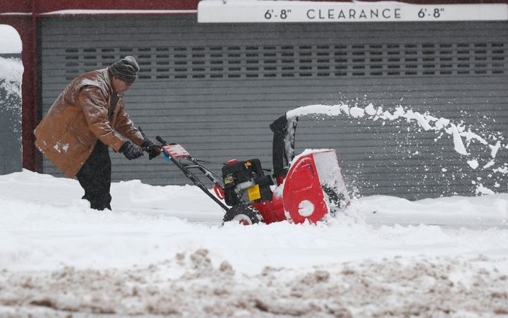A maintenance man uses a snowblower to clear a sidewalk outside a condominium complex along Grant Street as a storm packing s