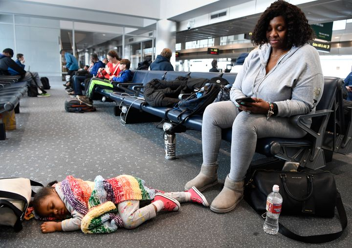 Sonya Washington, right, checks her phone while her granddaughter Nora Lyrse, 2, sleeps comfortably at her feet at the Denver
