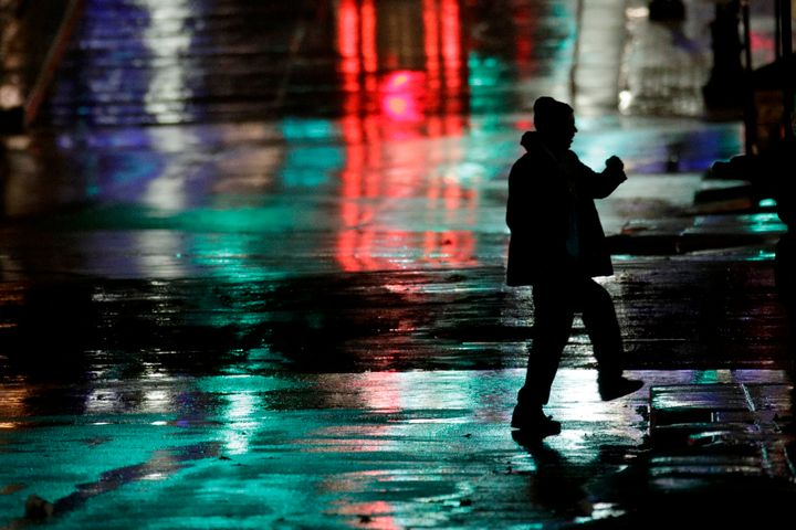 A man is silhouetted as he crosses a rain-covered street on a cold windy night on Nov. 26, 2019, in Kansas City, Mo. The area