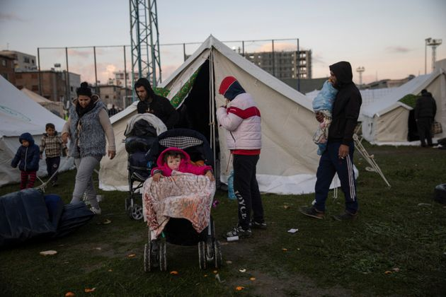 People stand outside a tent at a makeshift camp at a soccer field in Durres, western Albania, on Nov....