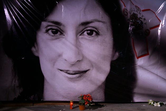 Flowers and a candle lie in front of a portrait of slain investigative journalist Daphne Caruana Galizia...