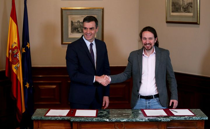 Spanish Prime Minister Pedro Sánchez and Unidas Podemos leader Pablo Iglesias shake hands during a news conference on
