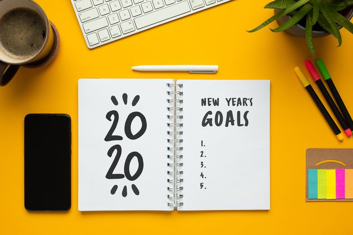 Stock photo of 2020 new year notebook with list of goals and objects on yellow background