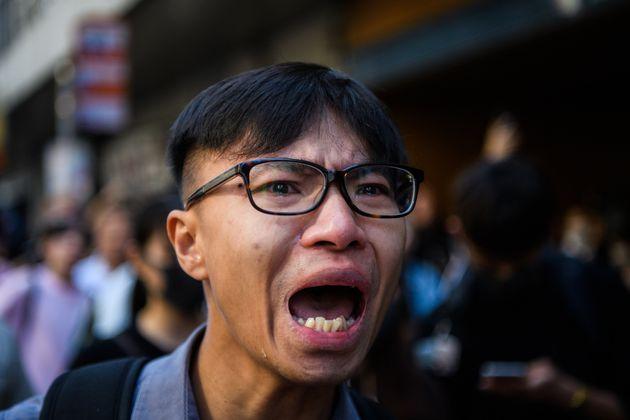 Un homme pleure en criant des slogans à la police près du site où un manifestant...