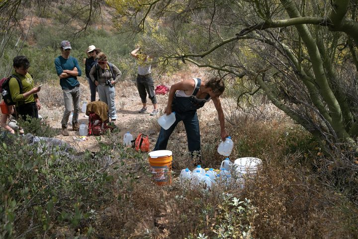 A volunteer for the humanitarian aid organization No More Deaths delivers water along a trail used by undocumented immigrants