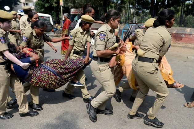 Police personnel detain activists during a protest against the state government's order to sack over...