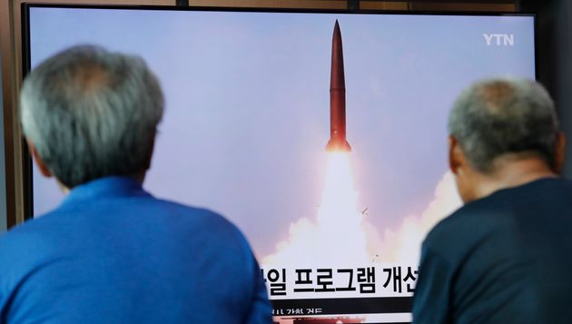 People watch a TV showing a file image of North Korea's missile launch during a news program at the Seoul...
