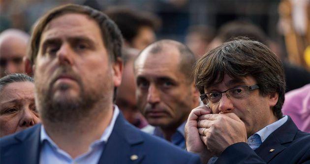 Carles Puigdemont, expresidente catalán, habla discretamente por el móvil detrás de Oriol Junqueras (ERC),...