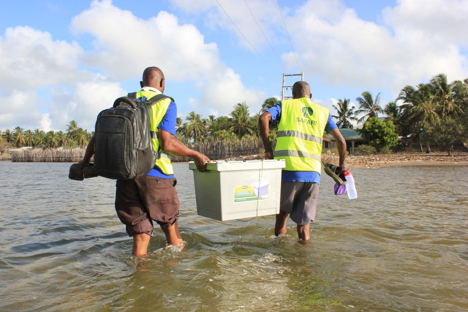 Safari Doctors carry supplies ashore at one of the stops on their route. The group sets up mobile clinics in each village for a few hours before moving on to the next stop. Each night, they camp out under the stars with people from the community.