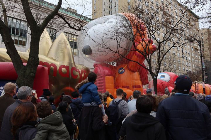 People walk past the Astronaut Snoopy balloon after it was inflated for the annual Macy's Thanksgiving Day Parade in New York