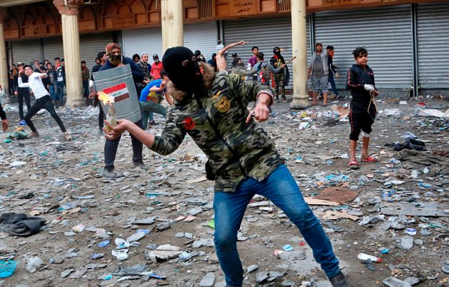 An anti-government protester prepares to throw a molotov cocktail toward security forces during clashes...