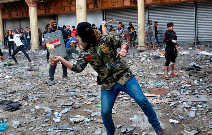An anti-government protester prepares to throw a molotov cocktail toward security forces during clashes on Rasheed Street in Baghdad, Iraq, on Nov. 28, 2019.