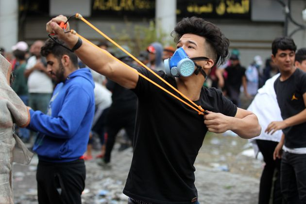 Iraqi protesters clash with Iraqi security forces in al-Rasheed Street during ongoing anti-government...