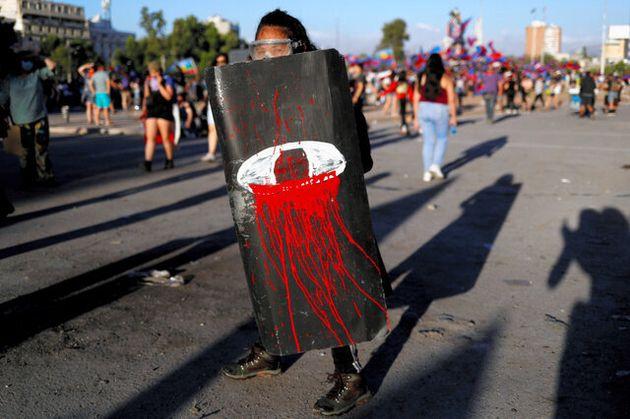 チリのサンティアゴで16日、血を流した目を描いた盾を持って抗議運動に参加する女性=ロイター