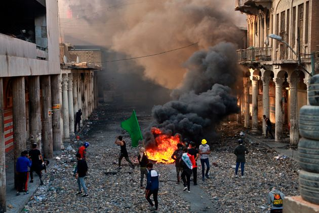 Anti-government protesters set fire while security forces close Rasheed Street during clashes in Baghdad,...
