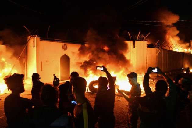 Iraqi demonstrators gather as flames start consuming Iran's consulate in the southern Iraqi Shiite holy...