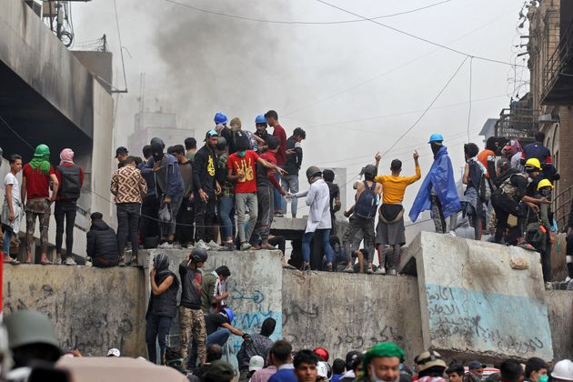 TOPSHOT - Iraqi protesters clash with Iraqi security forces in al-Rasheed Street during ongoing anti-government...