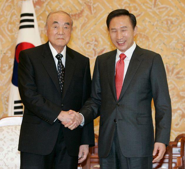 South Korea's new President Lee Myung-bak (R) shakes hands with former Japanese Prime Minister Yasuhiro...